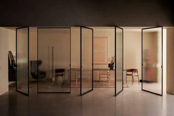 design glazen taatsdeuren of pivot deur met een zwart aluminium kader en bewerkt glas