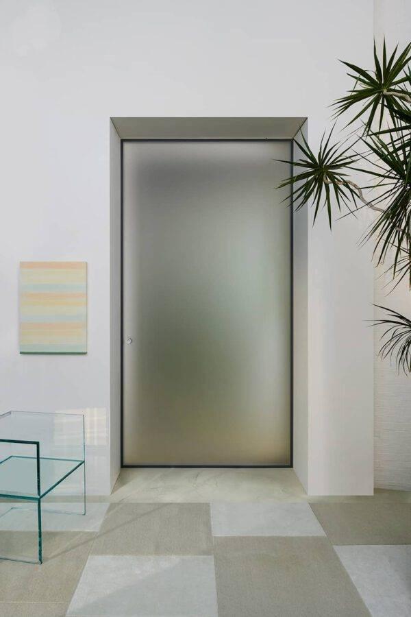 moderne glazen taatsdeur met gematteerd lichtdoorlatend glas en zwart aluminium kader ontworpen door piero lissoni voor glas italia Aladin Spin